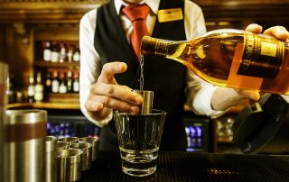waiter pouring scotch whisky after a days guided fly fishing in scotland