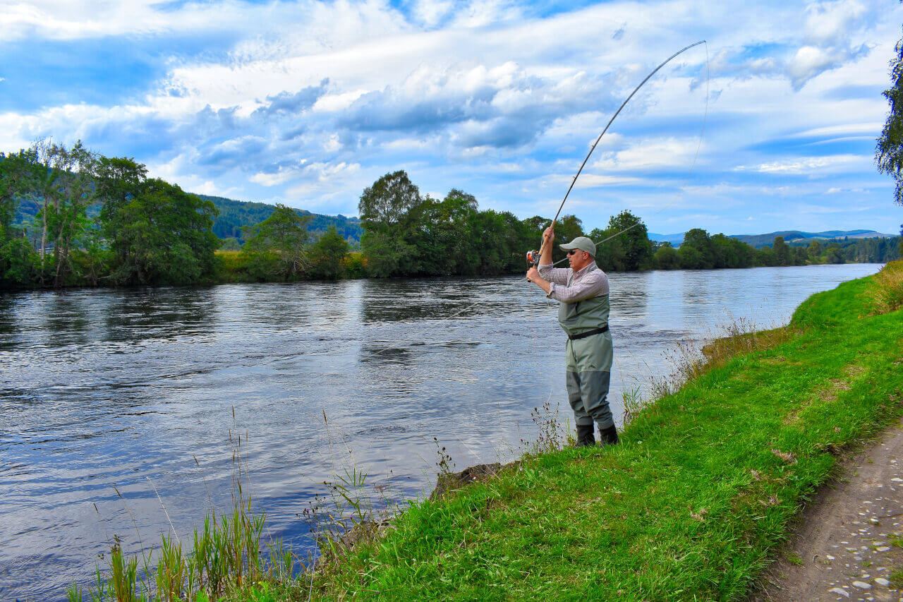 Fly casting on river during salmon fishing holiday